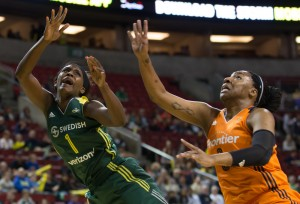Crystal Langhorne takes a foul from the Sun's Kelsey Bone on the way to the basket. (Neil Enns/Storm Photos)
