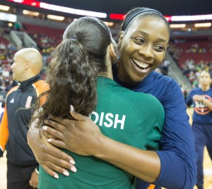 Former Seattle Storm player Camille Little hugs Sue Bird before meeting the game's honourary captains. (Neil Enns/Storm Photos)