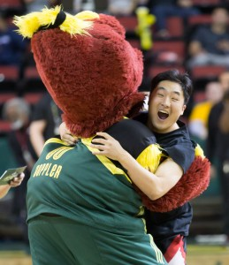 Dopper celebrates with a Storm fan after he wins the halfcourt shooting competition. (Neil Enns/Storm Photos)