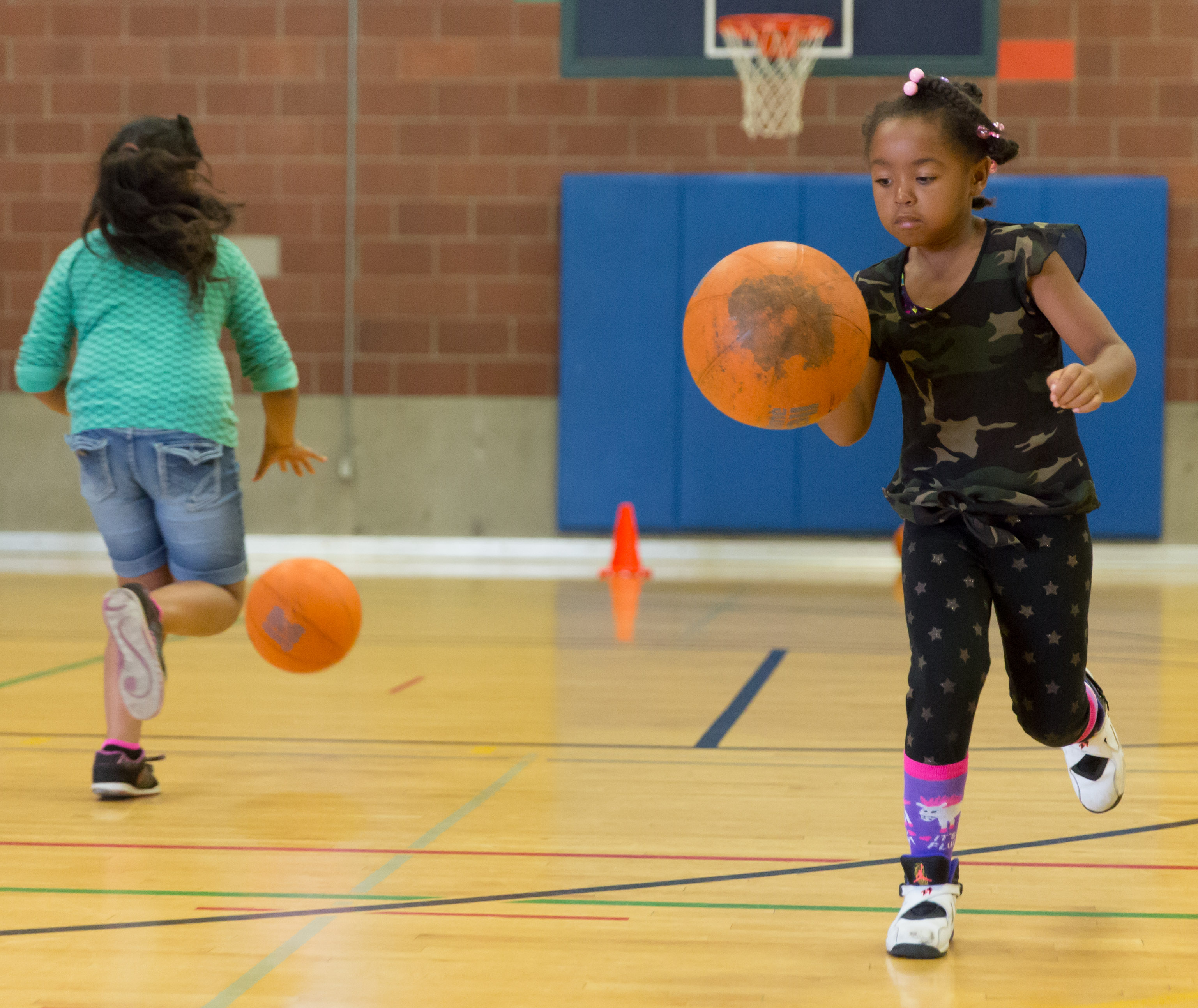 Two kids practice dribbling skills during a drill. (Neil Enns/Storm Photos)